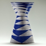 Slip cast moulded vase, exposed grey underglaze and blue matt glaze. The geometry of th is vase is created by three ovals one above the other.