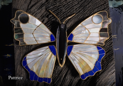 Pattrice - Le papillon - Le couteau est en jais avec une lame en acier damas multi-barreaux, à système pompe arrière, il fait 14cm ouvert. Il est posé sur une silhouette de papillon, en argent dorée à l'or fin. Les ailes sont réalisées en nacre blanche, nacre jaune, nacre noire et lapis lazuli. Les ailes sont amovibles et sont posées sur un socle de Couëron âgé de 8000ans, celui-ci repose sur une laque faite de feuilles d'or et de poudre de nacre